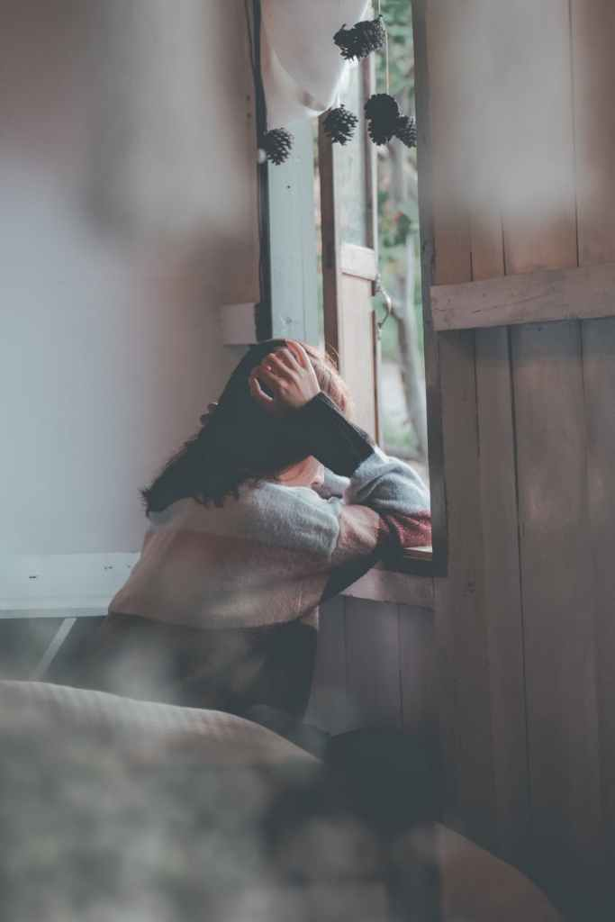photo of a person leaning on wooden window